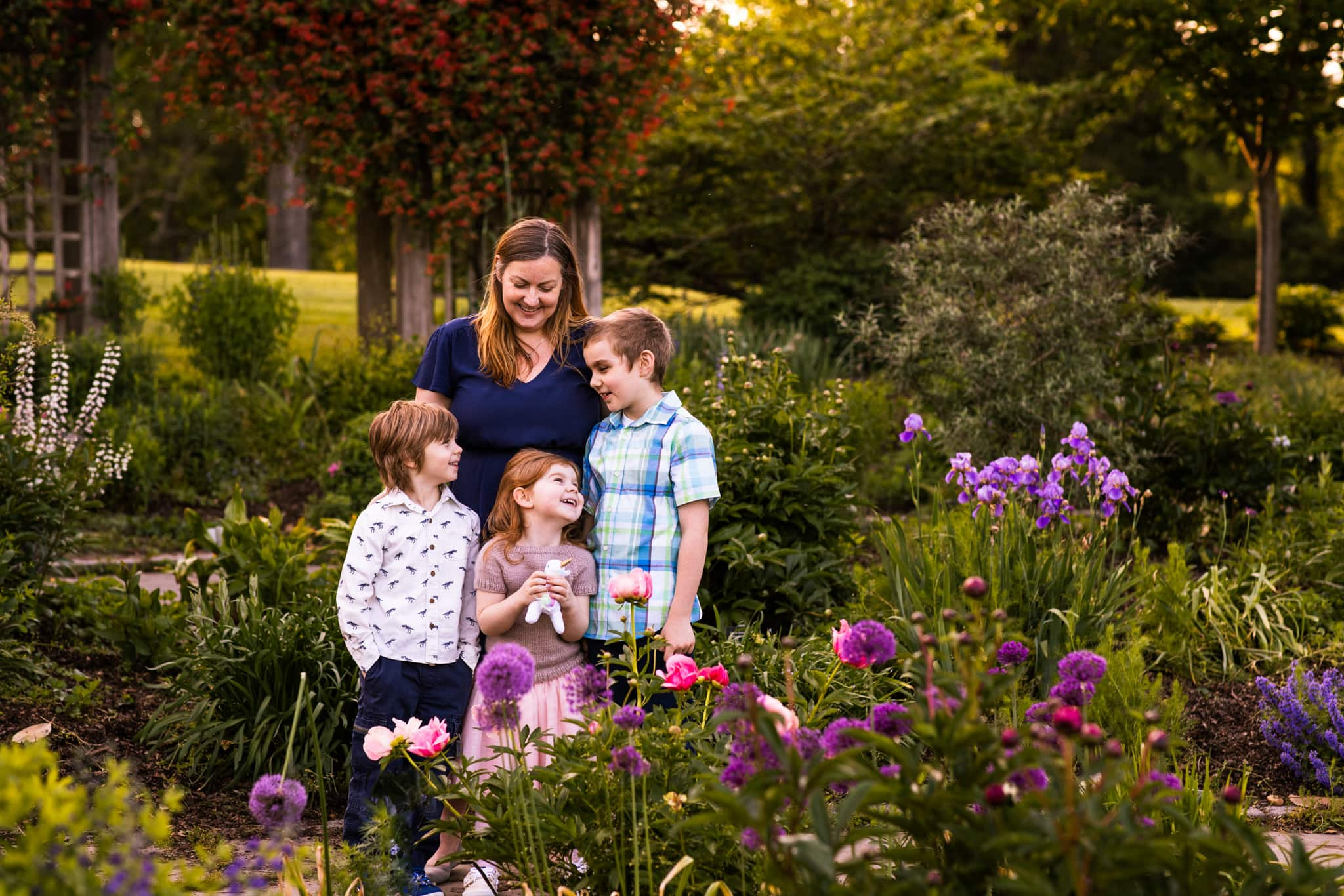 mom stands with 3 kids in garden flowers