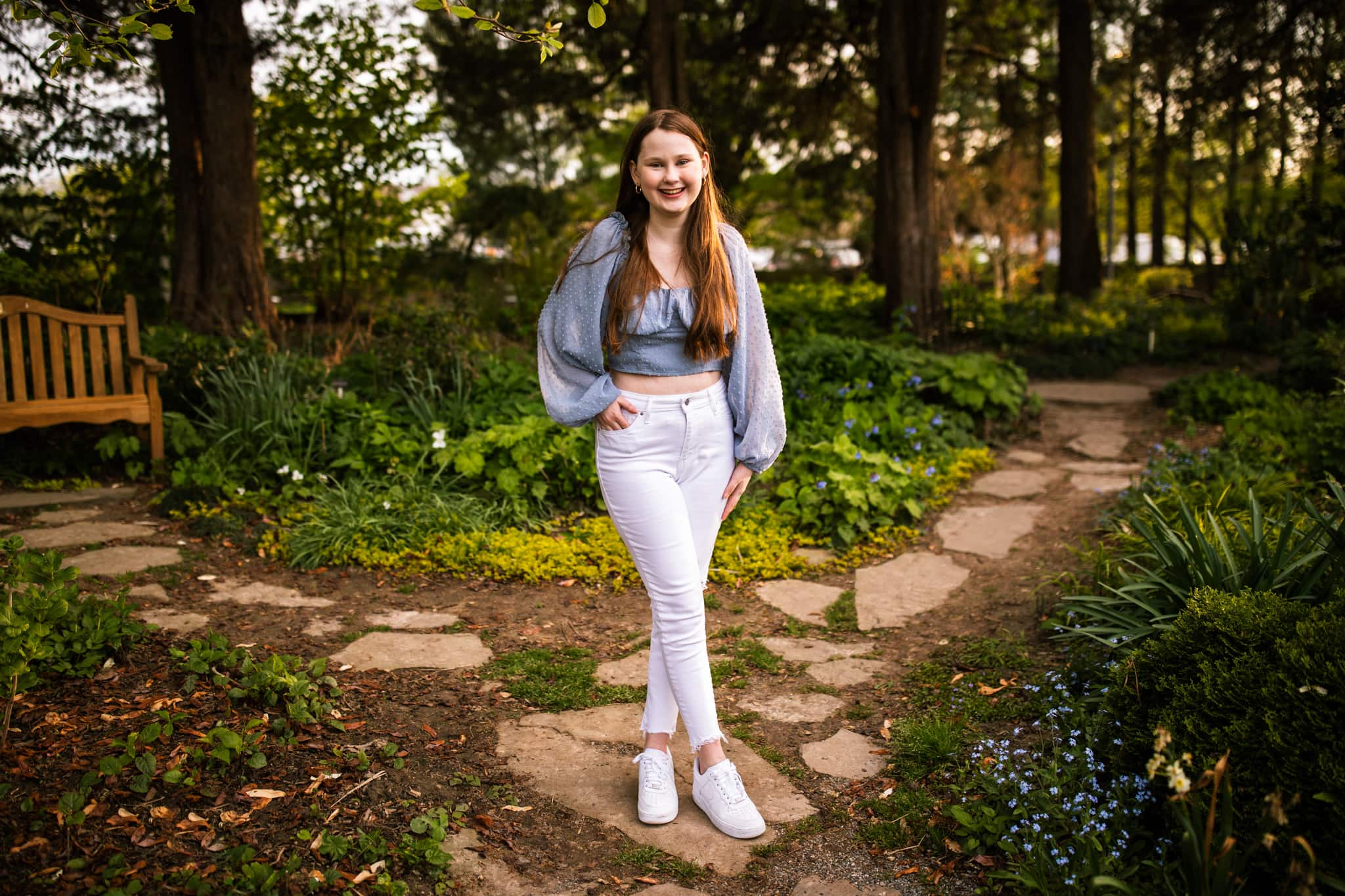 high school senior girl smiles along pathway