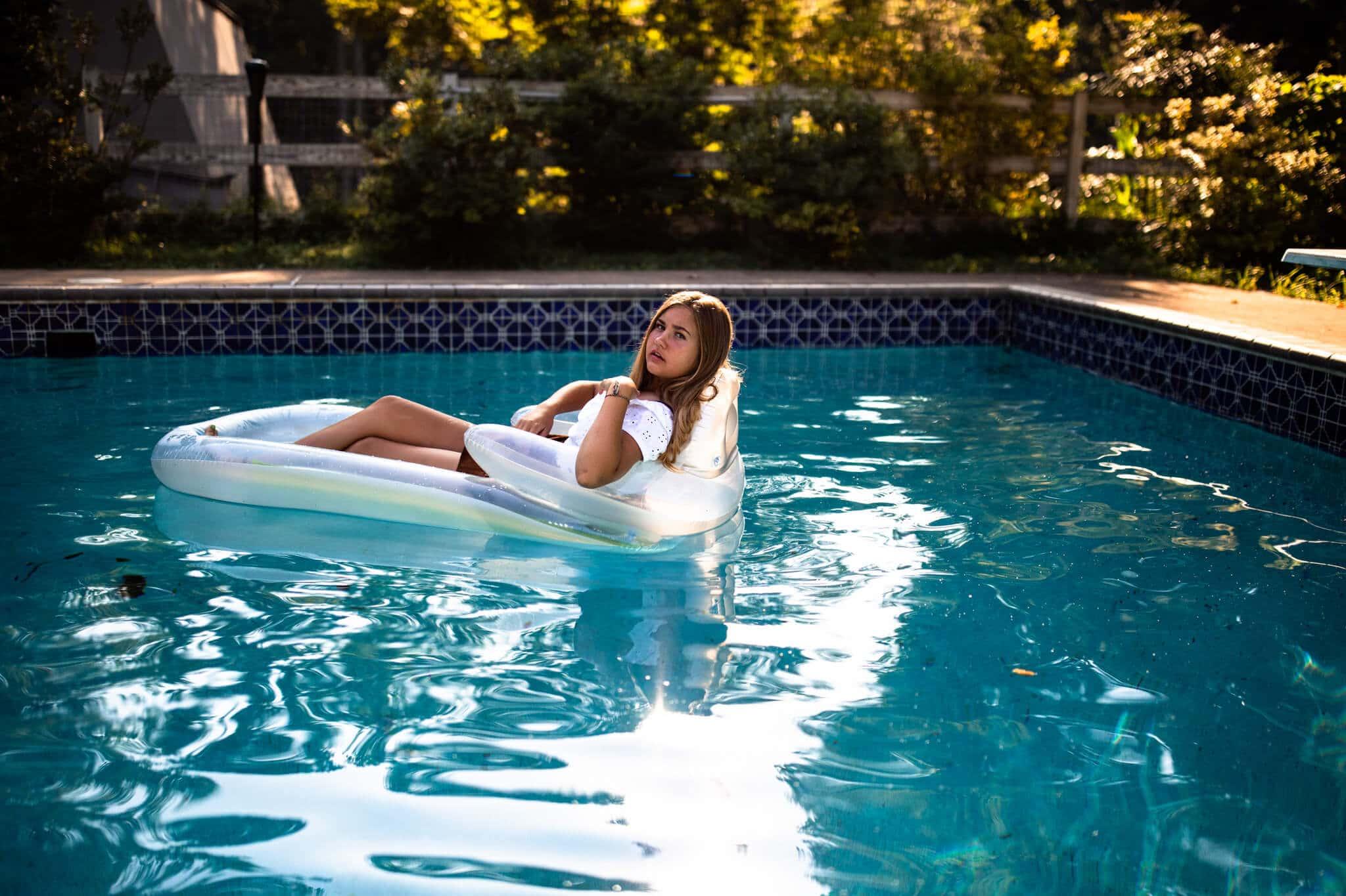 senior girl floats on pool raft