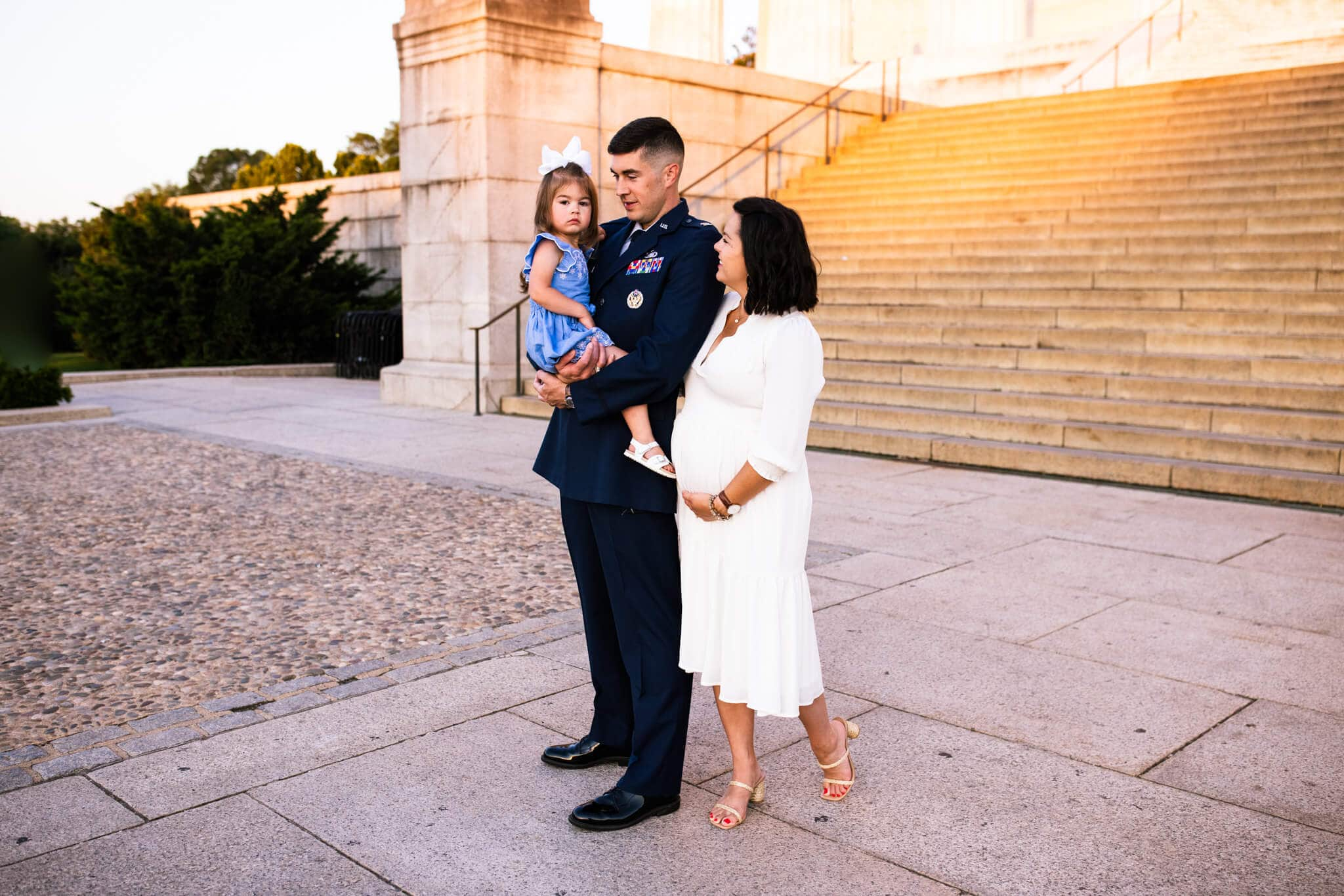 mom and dad stand with toddler daughter in front of Lincoln Memorial steps