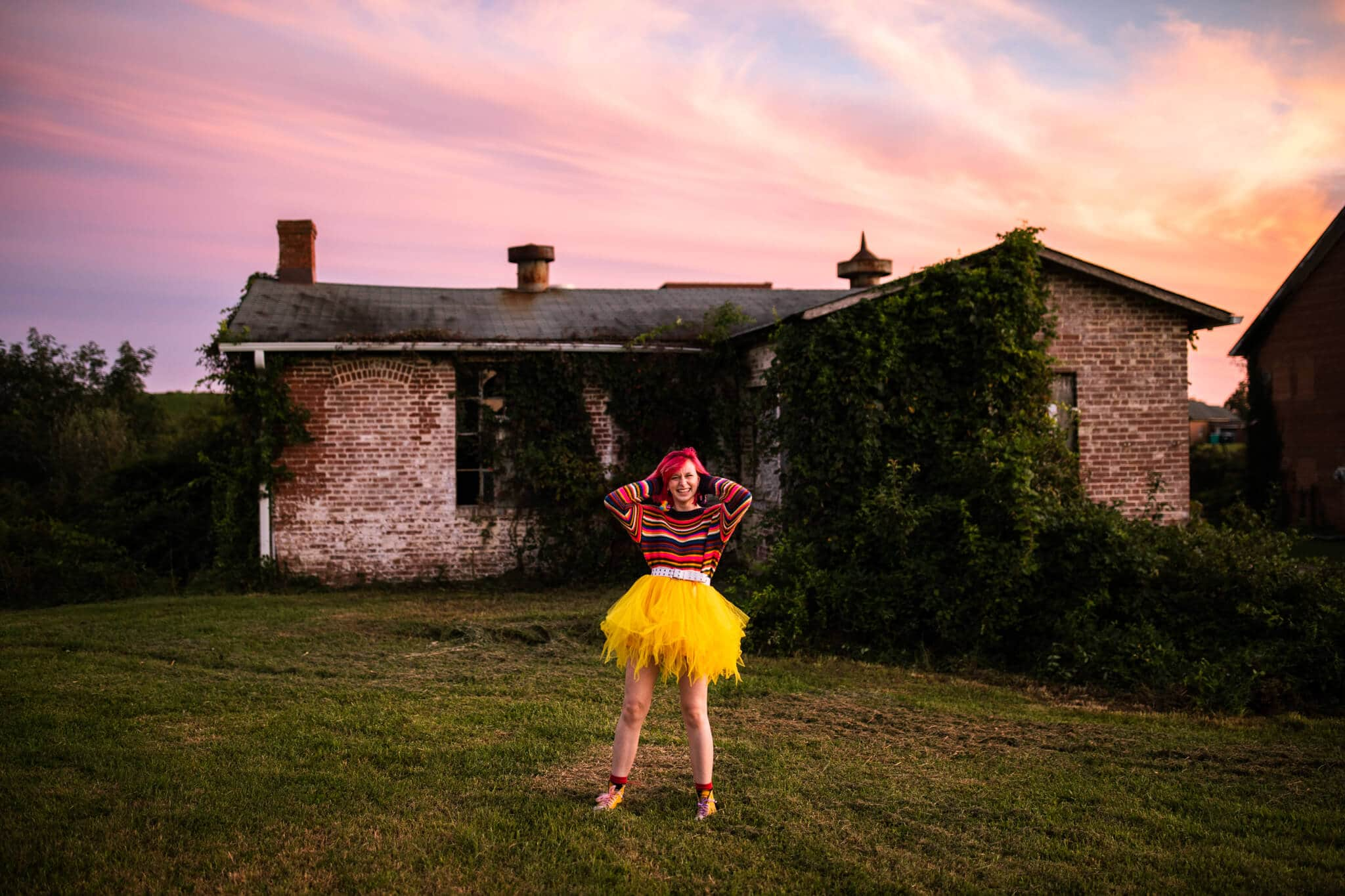 high school senior girl with pink hair and yellow skirt smiles in front of pink sky