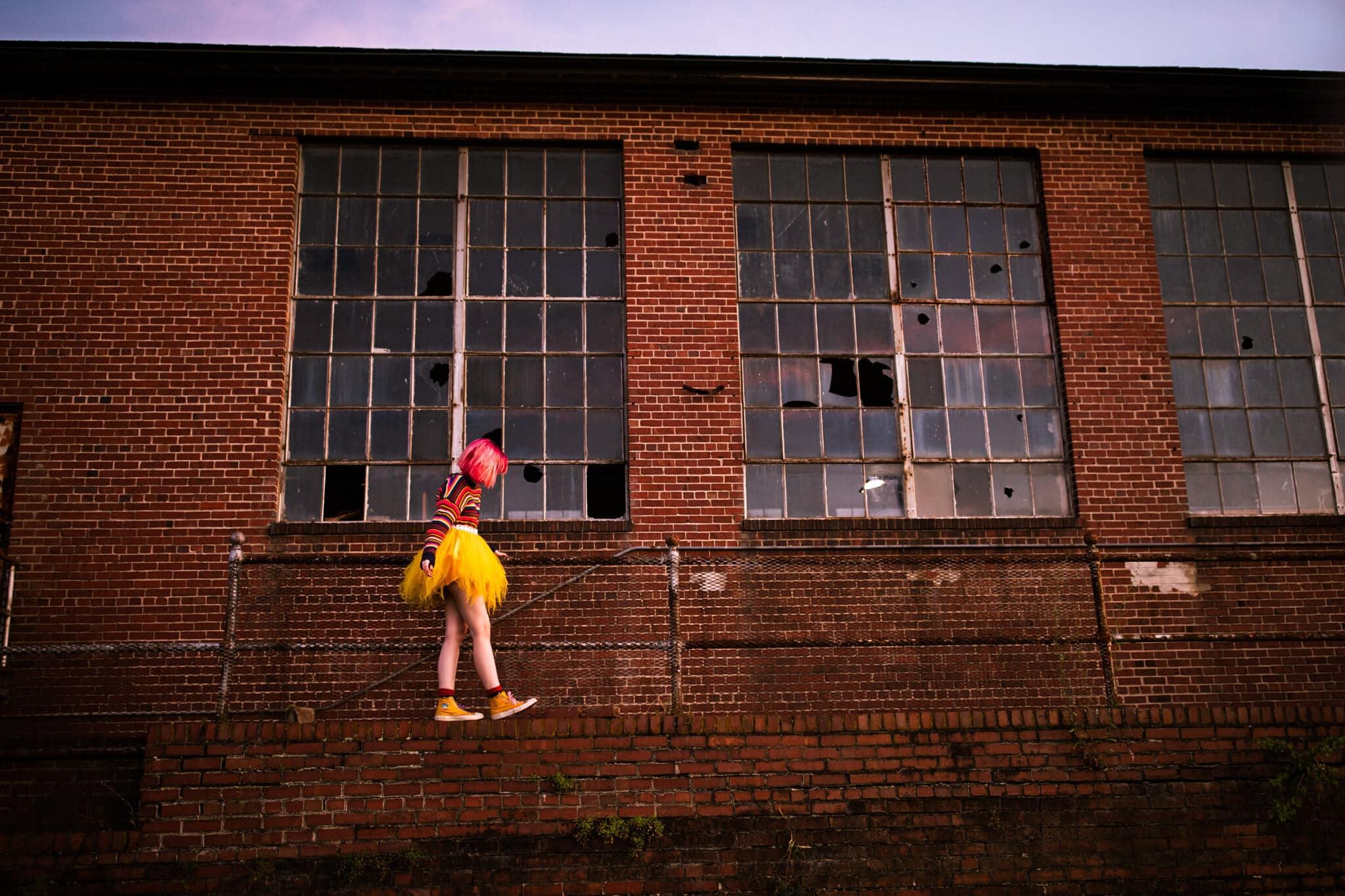 high school senior girl walks along abandoned building