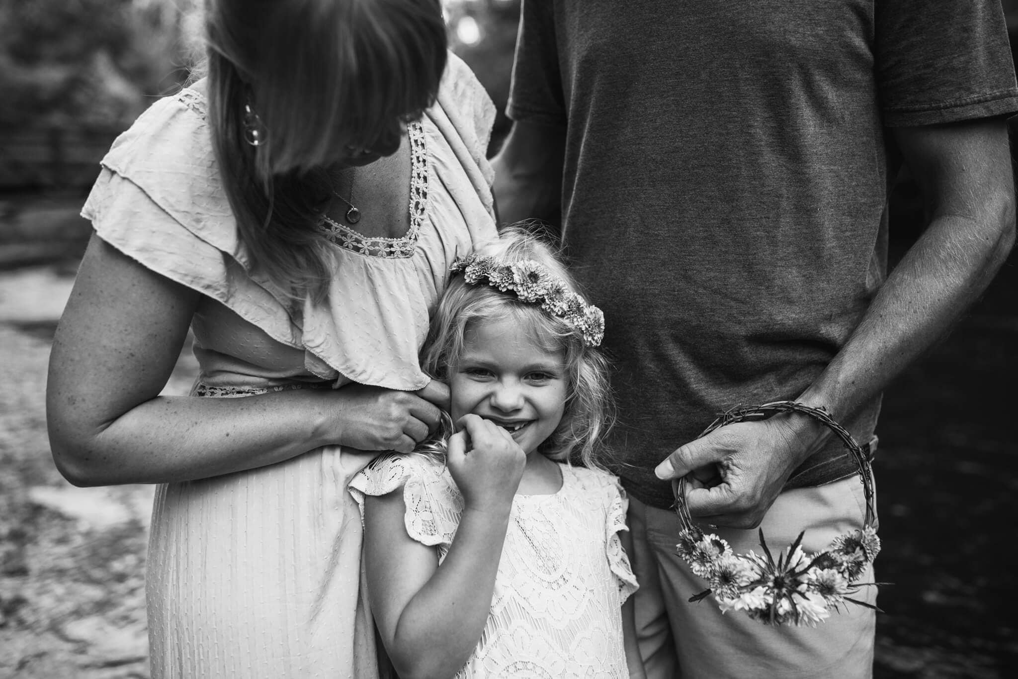black and white image of daughter is tickled by parents