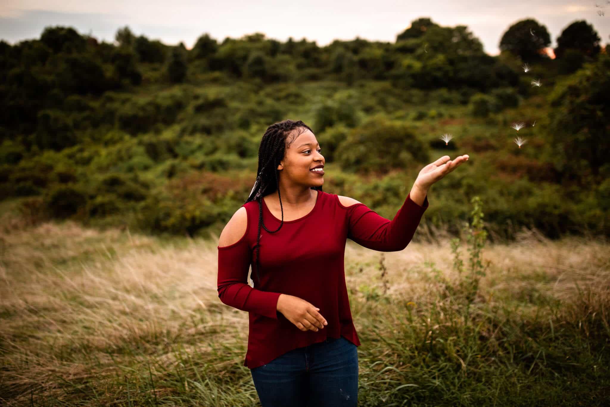 high school senior girl holds milkweed in field