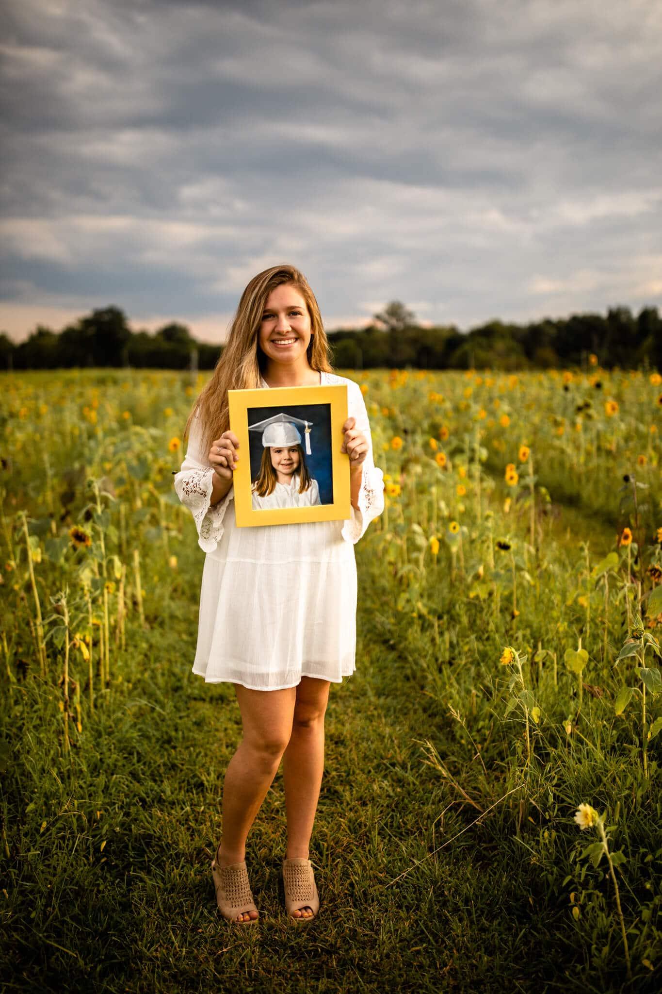 senior girl holds preschool grad photo in sunflower field