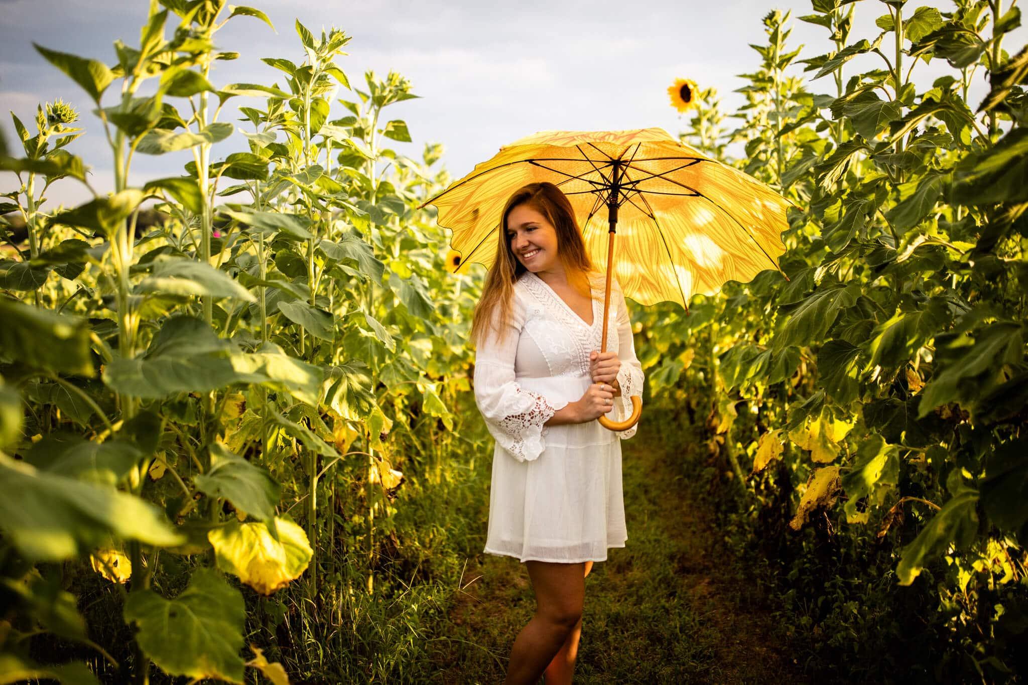 high school senior girl with sunflower umbrella in sunflower field