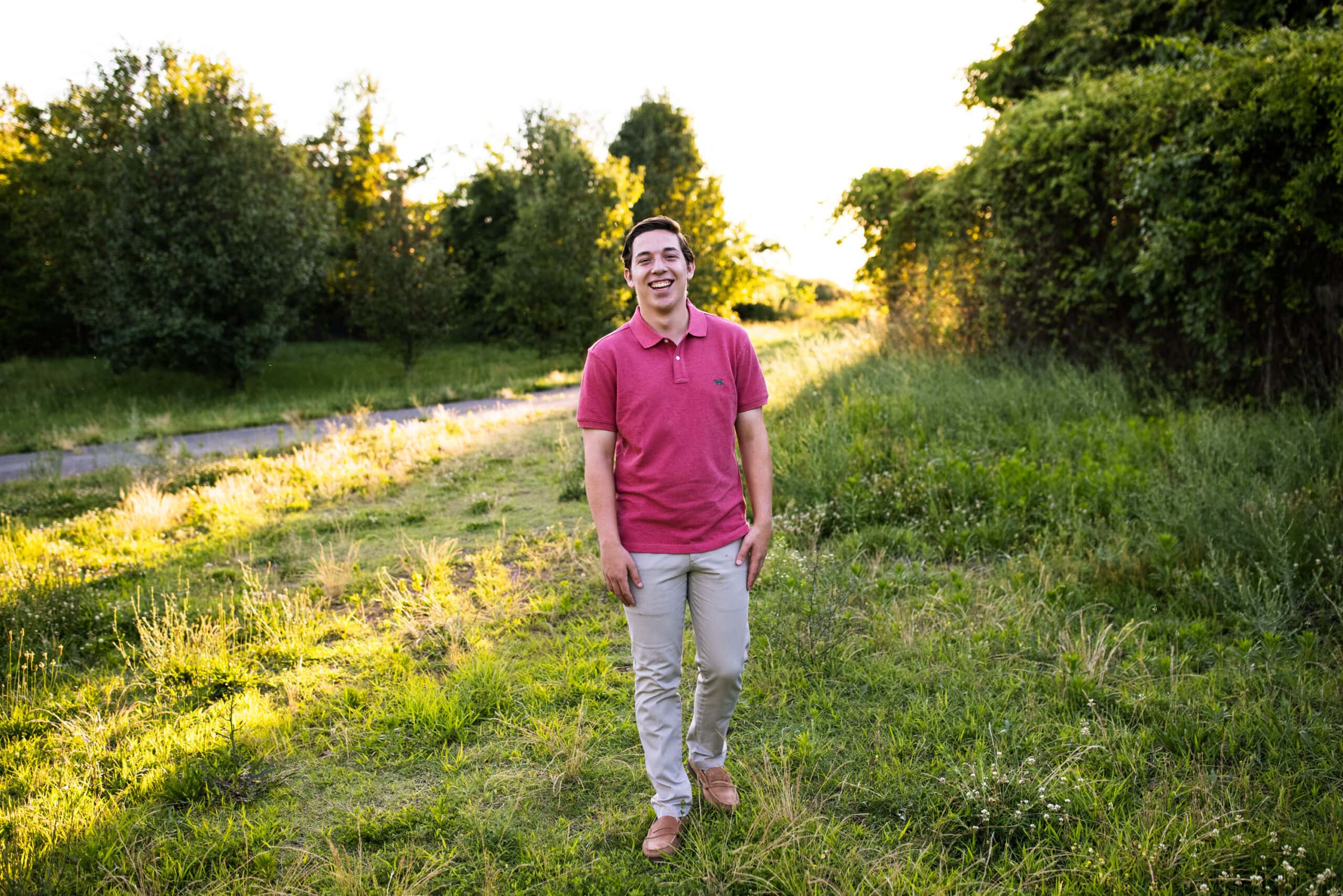 high school graduate walking in field with long shadows and sun behind