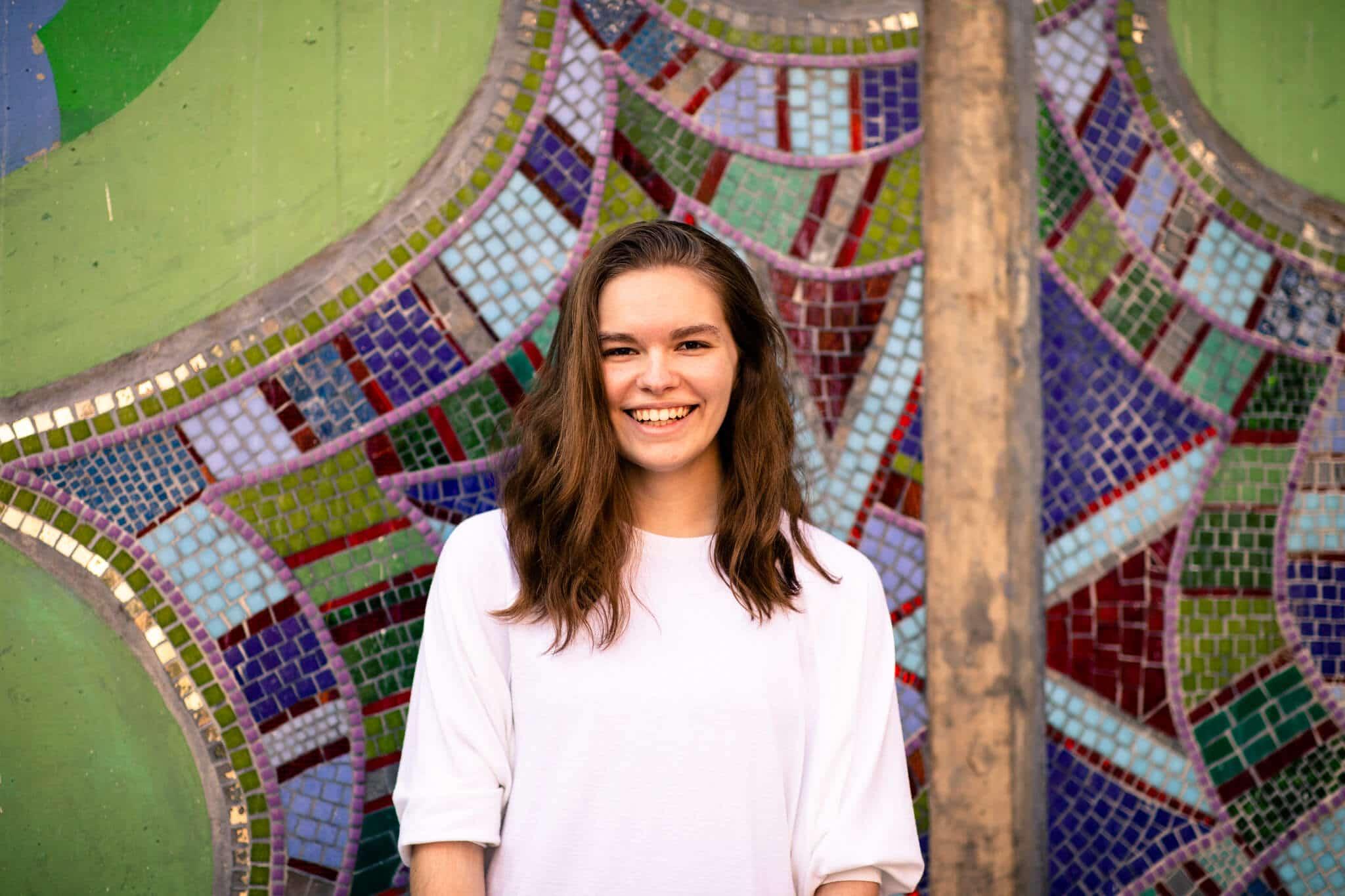 high school senior girl against mosaic wall