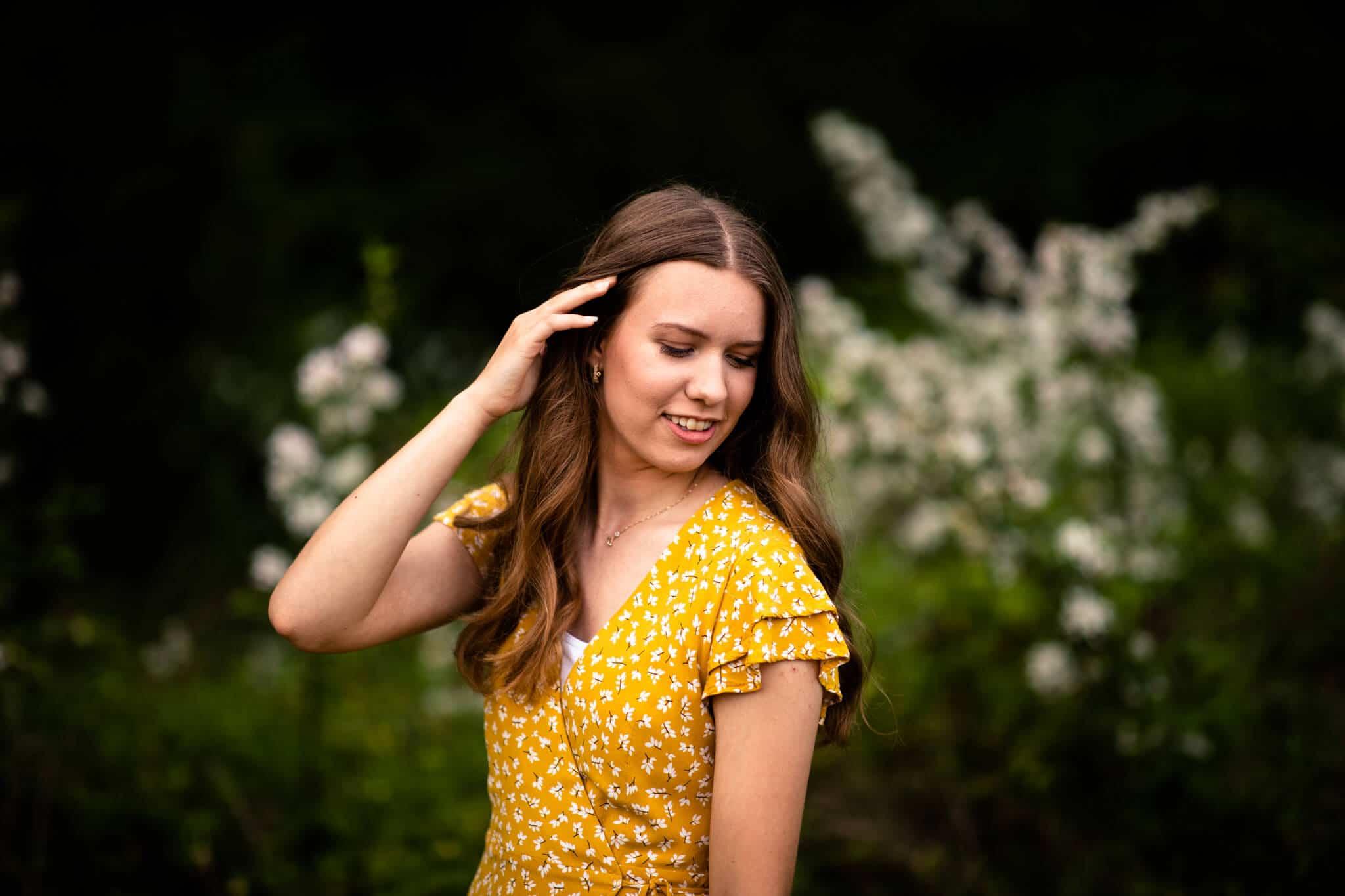 senior girl puts hair behind ear