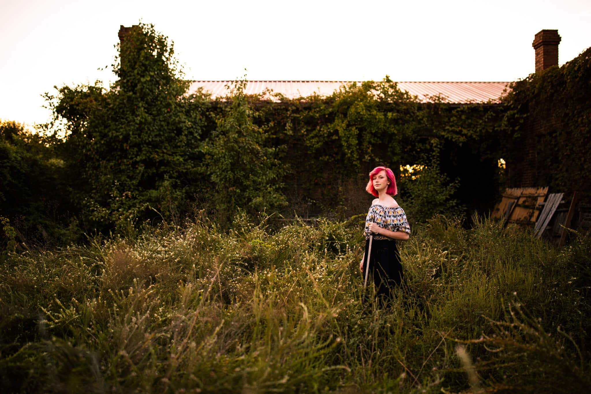 high school senior girl with pink hair in field
