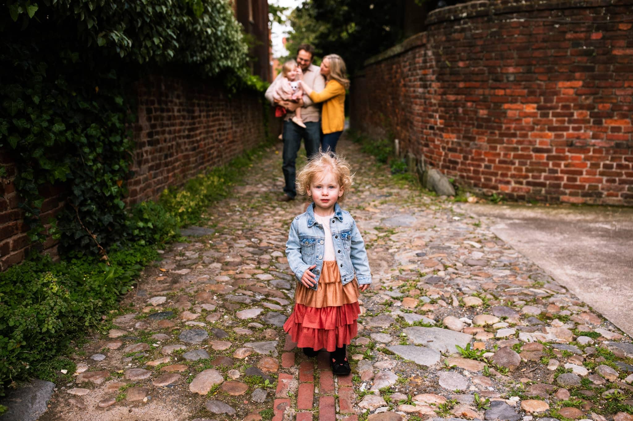 little girl runs toward camera in old town alexandria
