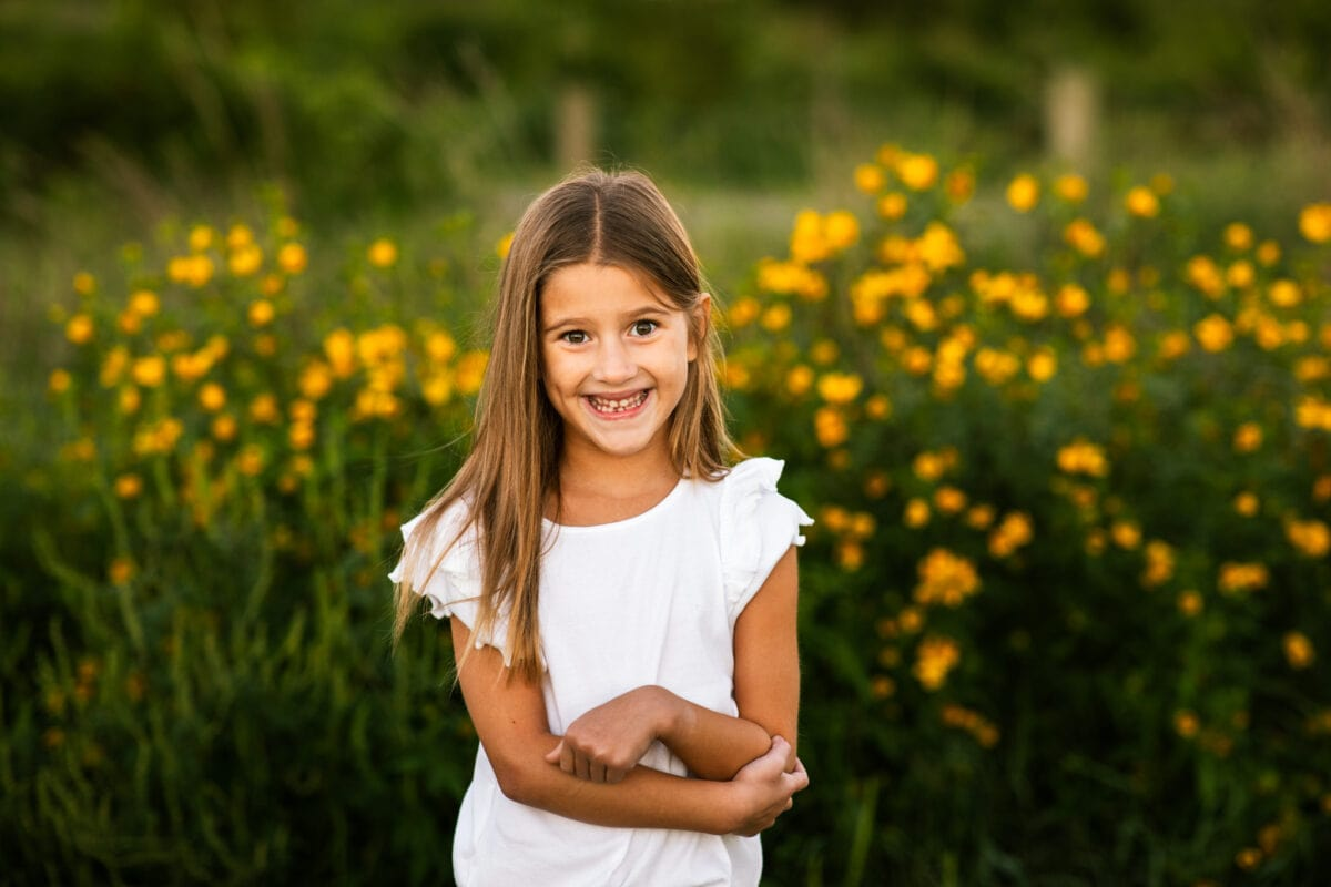 girl with white shirt in front of a field of yellow flowers