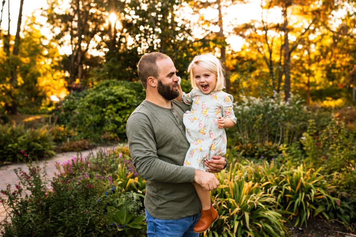 dad holding toddler daughter in garden setting