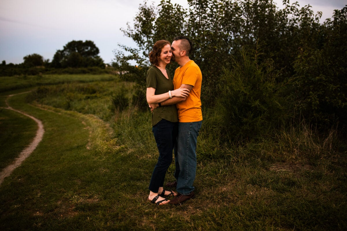couple standing and cuddling together along path