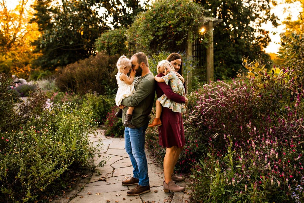 parents holding toddler girls, hugging on garden path
