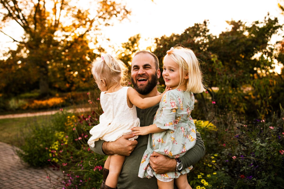 dad holding 2 daughters laughing
