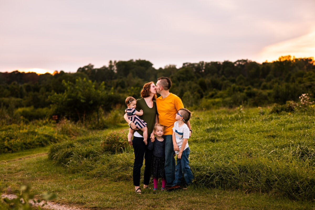 family of 5 standing in open field, parents kissing