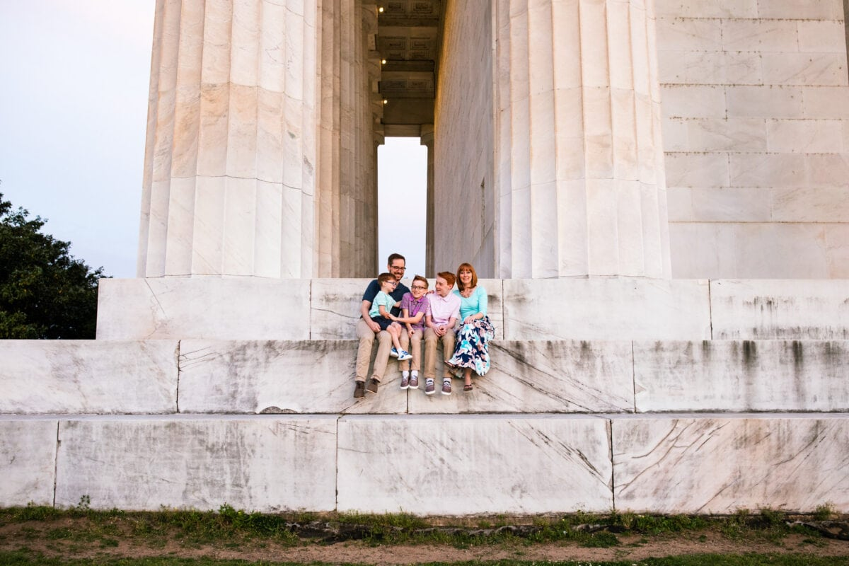 family sits together on large steps on Lincoln Memorial