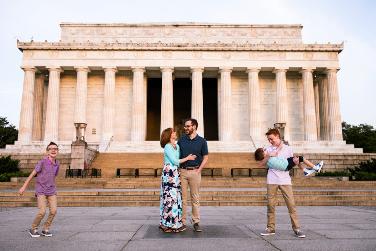 family of 5 plays in front of Lincoln Memorial at sunrise