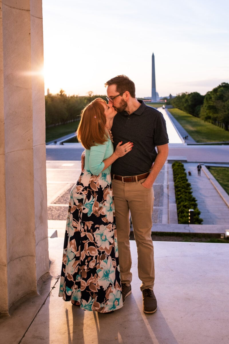 couple kissing at sunrise with Reflecting Pool in background