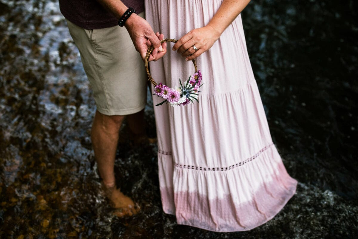 husband and wife stand in creek with symbolic flower crown