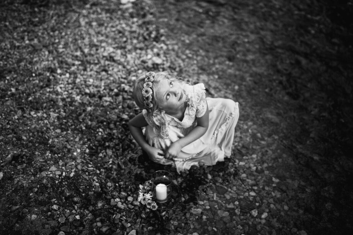 black and white image of girl playing by creek