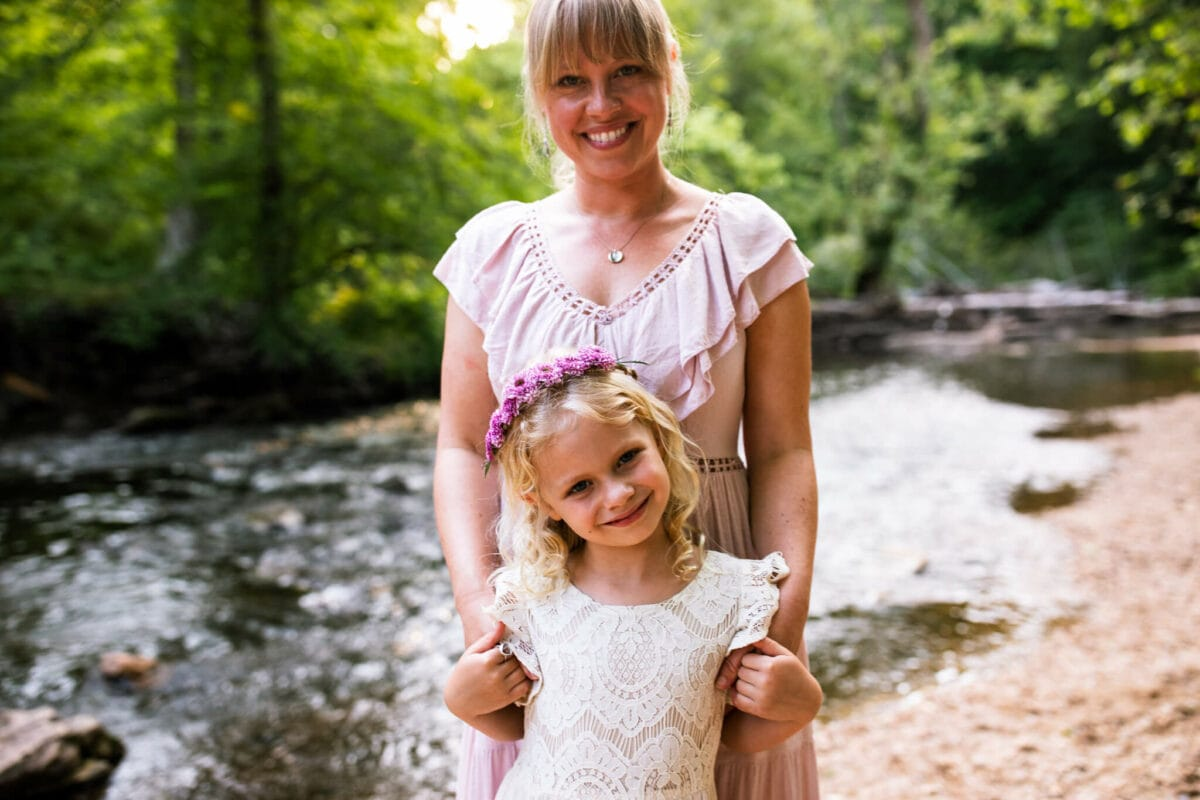 mother and daughter stand together at edge of creek