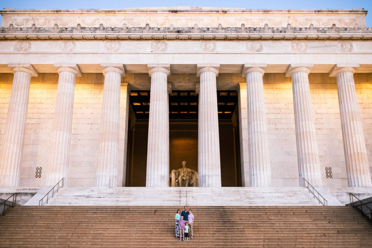 family of 5 on steps with entire Lincoln Memorial in background at sunrise