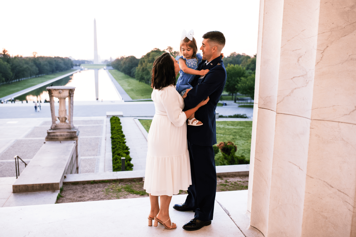 family with toddler daughter on steps of Lincoln Memorial with Washington Monument in background