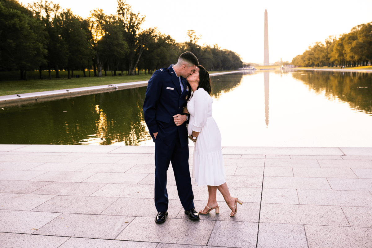 Husband kisses pregnant wife in front of Reflecting Pool