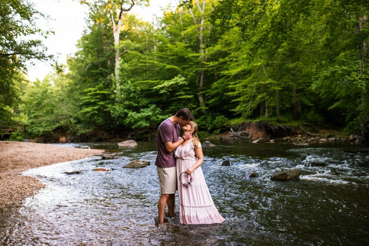 husband and wife kiss in creek
