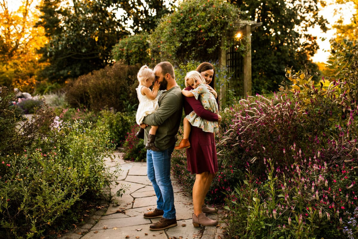 family stands in garden smiling at each other and camera