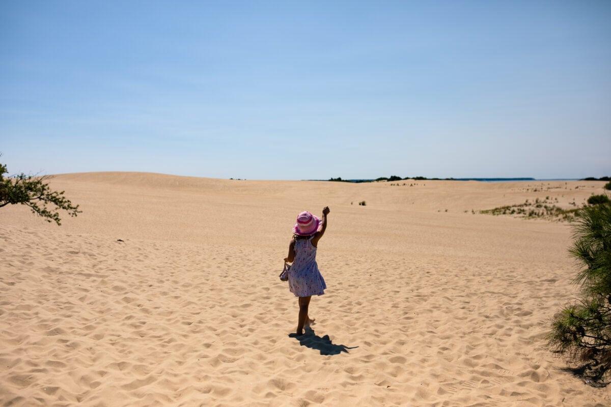 girl raises hand while walking on sand dune