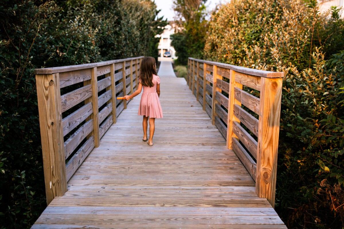 girl walking away from camera on boardwalk